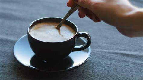Cinemagraph of person mixing sugar in coffee cup Stock